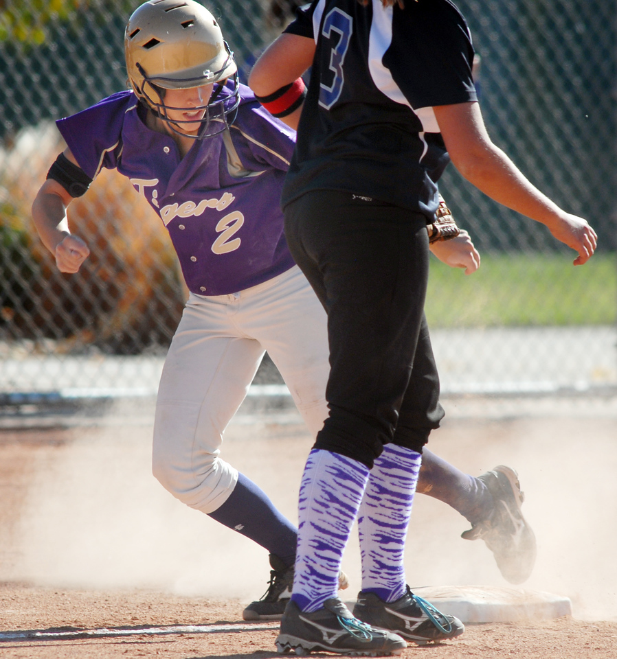 Holy Family's Beth Peterson touches third base while making a run to home past Mikey Cross, Middle Park, during state regional play at the Broomfield Industrial Park on Saturday.<br /> <br /> October 16, 2010<br /> staff photo/David R. Jennings
