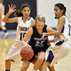 Holy Family's Katie Chavez, left, and Lindsey Chavez, box in Mountain Range's Rio Mitchell from moving down court during the game on Thursday at Holy Family.<br /> <br /> November 29, 2012<br /> staff photo/ David R. Jennings