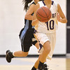 Katie Chavez, Holy Family, dribbles the ball down court past Hope Martinez, Mountain Range during Thursday's game at Holy Family.<br /> <br /> November 29, 2012<br /> staff photo/ David R. Jennings