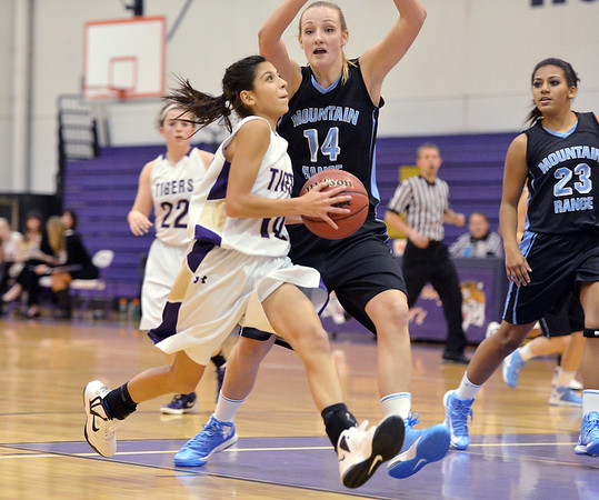 Katie Chavez, Holy Family, goes to the basket against Tory Travers, Mountain Range during the game on Thursday at Holy Family.<br /> <br /> November 29, 2012<br /> staff photo/ David R. Jennings