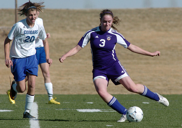 Holy Family's Heidi Hanson kicks the ball to the goal past Resurrection Church's Sarah Wallman during Wednesday's game in Loveland.<br /> March 22, 2011<br />  staff photo/David R. Jennings