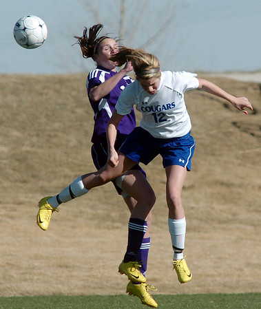 Holy Family's Kendall Russell goes for a header against Resurrection Church's Courtney Peterson during Wednesday's game in Loveland.<br /> March 22, 2011<br />  staff photo/David R. Jennings