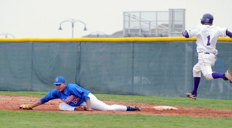 Holy Family's Matt Erb jumps to firstbase past Sheridan's Nick Garcia during Saturday's 3A district game at Holy Family.<br /> <br /> May 12, 2012 <br /> staff photo/ David R. Jennings