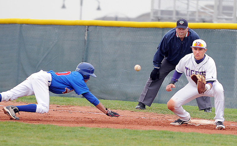 Holy Family's Garrett West wait to catch the ball while Sheridan's Joseph Pasillas slides to first during Saturday's 3A district game at Holy Family.<br /> <br /> May 12, 2012 <br /> staff photo/ David R. Jennings