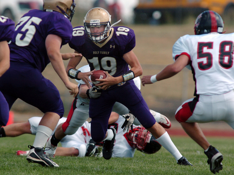 Quarterback Zach Langfield, Holy Family, keeps the ball while evading the tackle by Tanner Anderson, Steamboat Springs, during Satuday's game at Mike G. Gabriel Stadium.<br /> <br /> September 4, 2010<br /> staff photo/David R. Jennings