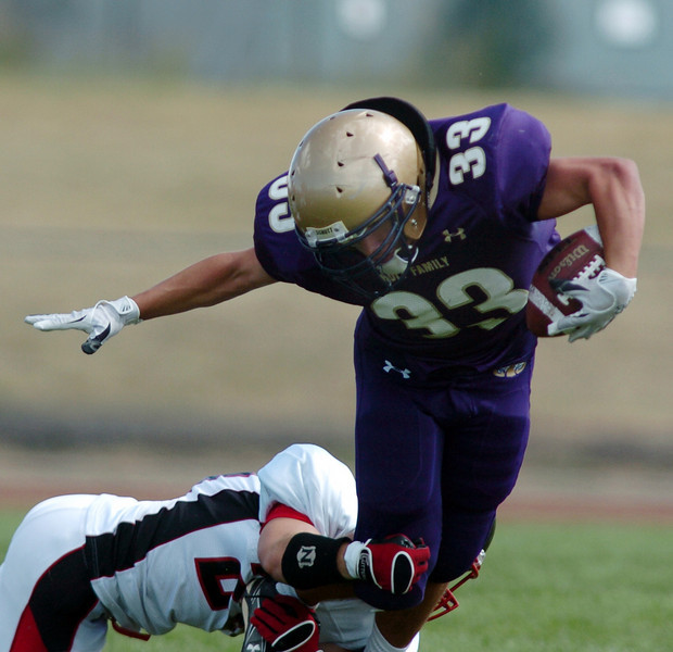 Connor Clay, Holy Family, gains yardage despite a tackle by Steamboat Springs during Satuday's game at Mike G. Gabriel Stadium.<br /> <br /> September 4, 2010<br /> staff photo/David R. Jennings