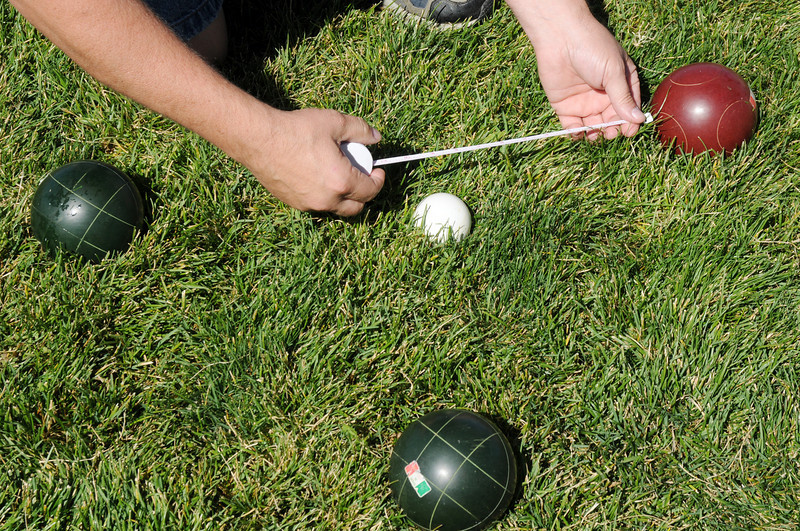 A judge measures the distance between a red ball and the pallino ball which is the target during a game in Saturday's Bocce tournament for Holy Family High School .<br /> <br /> September 25, 2010<br /> staff photo/David R. Jennings