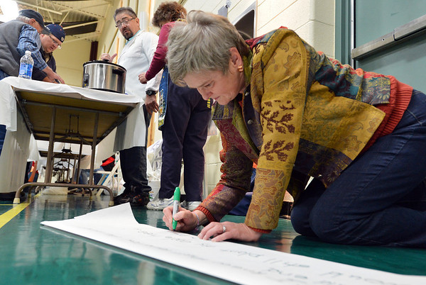 Debra Engquist, pastor of Atonement Lutheran, writes a quote by Martin Luther for her booth  during the Holy Smokes Clergy Cook-Off fundraiser for Flatirons Habitat for Humanity at the Broomfield United Methodist Church on Saturday. <br /> November 10, 2012<br /> staff photo/ David R. Jennings