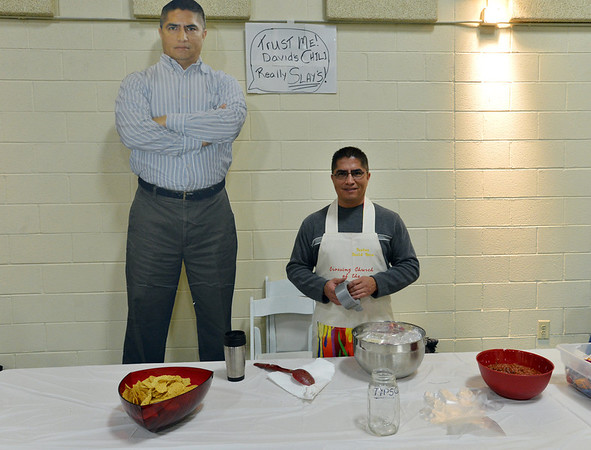 David Baca, connecting pastor  for the Crossing Church of the Nazarene, poses beside a giant photo of himself, while waiting to serve his family recipe of Chili Verde Caldo during the Holy Smokes Clergy Cook-Off fundraiser for Flatirons Habitat for Humanity at the Broomfield United Methodist Church on Saturday. <br /> November 10, 2012<br /> staff photo/ David R. Jennings