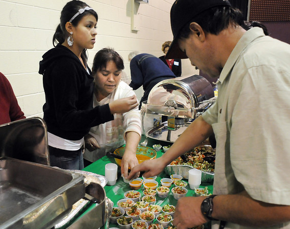 Future Habitat homeowner Maria Alcantar, center, with her daughter Ema, 13, left, and Juan Alcantar, right, prepare their food at the 5th Annual Holy Smokes Clergy Cook-off benefiting Flatirons Habitat For Humanity at the Broomfield United Methodist Church on Saturday.<br /> More than 350 people attended raising about $3,500 at the door and on tips. The winner of the cook-off was Pete Smith of Broomfield United Methodist Church. <br /> February 6, 2010<br /> Staff photo/David R. Jennings