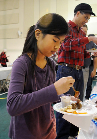 Natalie Buchold, 10, puts sauce on meatballs at the 5th Annual Holy Smokes Clergy Cook-off benefiting Flatirons Habitat For Humanity at the Broomfield United Methodist Church on Saturday.<br /> <br /> February 6, 2010<br /> Staff photo/David R. Jennings