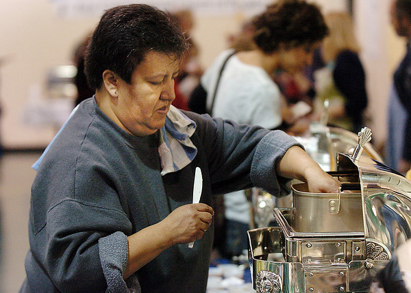 Leticia Agullera, future Habitat homeowner, prepares her food for attendees at the 5th Annual Holy Smokes Clergy Cook-off benefiting Flatirons Habitat For Humanity at the Broomfield United Methodist Church on Saturday.<br /> <br /> February 6, 2010<br /> Staff photo/David R. Jennings