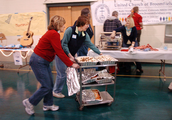 Volunteers Kathy Baker, left, and Phillys Rohnke wheel in a cart of food to a booth at the 5th Annual Holy Smokes Clergy Cook-off benefiting Flatirons Habitat For Humanity at the Broomfield United Methodist Church on Saturday.<br /> <br /> February 6, 2010<br /> Staff photo/David R. Jennings