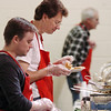 Rev. Thomas Cross, right, with volunteer Sean Caffery sample food while waiting to serve people at the 5th Annual Holy Smokes Clergy Cook-off benefiting Flatirons Habitat For Humanity at the Broomfield United Methodist Church on Saturday.<br /> <br /> February 6, 2010<br /> Staff photo/David R. Jennings