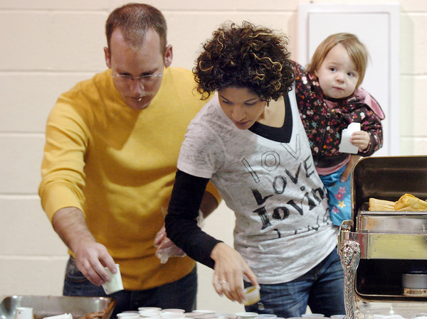 Clinton Moore, left, with his wife Pahtyana and daughter Ellyana, 16 months-old, help prepare future Habitat homeowner Leticia Agullera's table at the 5th Annual Holy Smokes Clergy Cook-off benefiting Flatirons Habitat For Humanity at the Broomfield United Methodist Church on Saturday.<br /> <br /> <br /> February 6, 2010<br /> Staff photo/David R. Jennings