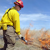 North Metro Fire Rescue District firefighter Eric Young prepares to put water on the western edge of a controlled burn to keep it contained to the 20 acres of the City and County fo Broomfield's Hoopes Farm at Lowell Blvd. and 144th Ave. on Wednesday. The burn was not only a training session for North Metro Wildland Team but also is being used as a weed control and  study by the county.<br /> <br /> <br /> March 17, 2010<br /> Staff photo/David R. Jennings