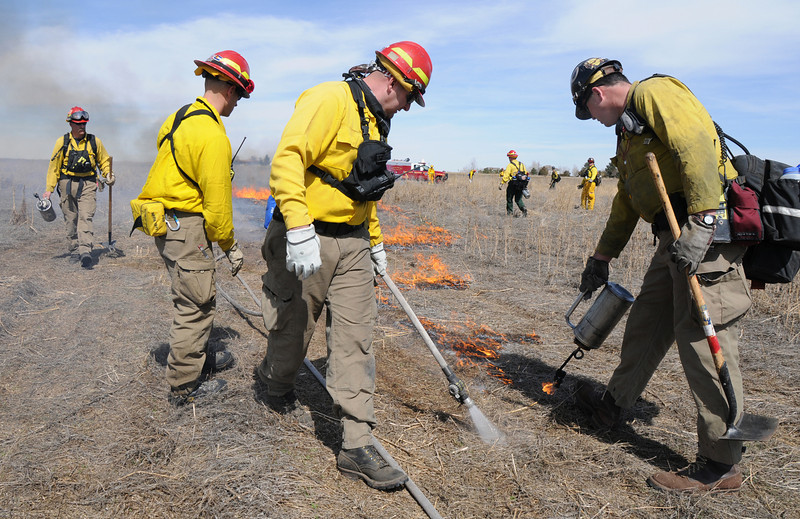 North Metro Fire Rescue District firefighters Eric Young, left and Brian LeFluer, center, with instructor Boulder firefighter Dave Zader, right, work the western edge of a controlled burn of 20 acres on the City and County of Broomfield's Hoopes Farm at Lowell Blvd. and 144th Ave. on Wednesday. The burn was not only a training session for North Metro Wildland Team but also is being used as a weed control study by the county.<br /> <br /> <br /> March 17, 2010<br /> Staff photo/David R. Jennings