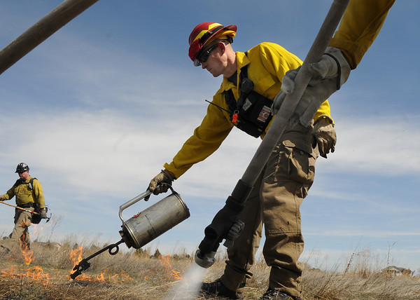 North Metro Fire Rescue District firefighter Eric Young uses a drip torch as Brian LeFleur puts water down as they work the western edge of a controlled burn of 20 acres of the City and County of Broomfield's Hoopes Farm at Lowell Blvd. and 144th Ave. on Wednesday. <br /> <br /> <br /> March 17, 2010<br /> Staff photo/David R. Jennings
