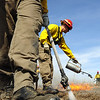 North Metro Fire Rescue District firefighter Eric Young uses a drip torch as Brian LeFleur puts water down as they work the western edge of a controlled burn of 20 acres of the City and County of Broomfield's Hoopes Farm at Lowell Blvd. and 144th Ave. on Wednesday. <br /> <br /> March 17, 2010<br /> Staff photo/David R. Jennings