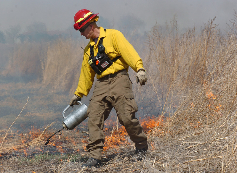 BE0317BURN08<br /> North Metro Fire Rescue District firefighter Eric Young uses a drip torch on a controlled burn of 20 acres on the City and County of Broomfield's Hoopes Farm at Lowell Blvd. and 144th Ave. on Wednesday. The burn was not only a training session for North Metro Wildland Team but also is being used as a weed control study by the county.<br /> <br /> <br /> March 17, 2010<br /> Staff photo/David R. Jennings