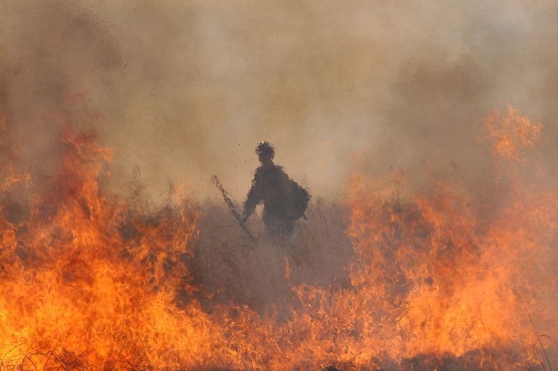 A firefighter walks through a safe area of the controlled burn by North Metro Fire Rescue District fon 20 acres of the City and County of Broomfield's Hoopes Farm at Lowell Blvd. and 144th Ave. on Wednesday. The burn was not only a training session for North Metro Wildland Team but also is being used as a weed control and study by the county. <br /> <br /> <br /> March 17, 2010<br /> Staff photo/David R. Jennings