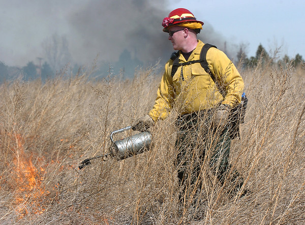 North Metro Fire Rescue District firefighter David Waller uses a drip torch on a controlled burn of 20 acres on the City and County of Broomfield's Hoopes Farm at Lowell Blvd. and 144th Ave. on Wednesday. The burn was not only a training session for North Metro Wildland Team but also is being used as a weed control study by the county.<br /> <br /> <br /> March 17, 2010<br /> Staff photo/David R. Jennings