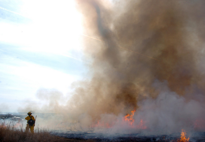 North Metro Fire Rescue District firefighter Steve Bostwick stands by as whirlwind, center, created by the fire, swirls during the controlled burn on the City and County of Broomfield's Hoopes Farm at Lowell Blvd. and 144th Ave. on Wednesday. <br /> <br /> <br /> March 17, 2010<br /> Staff photo/David R. Jennings