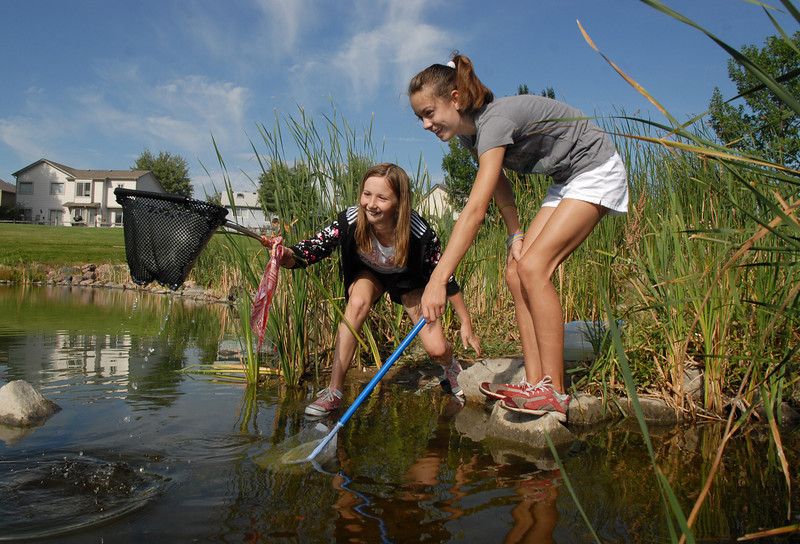 Mikayla Goodman, 11, left, and Carlie Preskitt, 11, try to catch minnows along the shore at the Broomfield Optimist Club's Huck Finn-Becky Thatcher Fishing Derby on Saturday at the Trails Pond. <br /> <br /> August 29, 2009<br /> staff photo/David R. Jennings