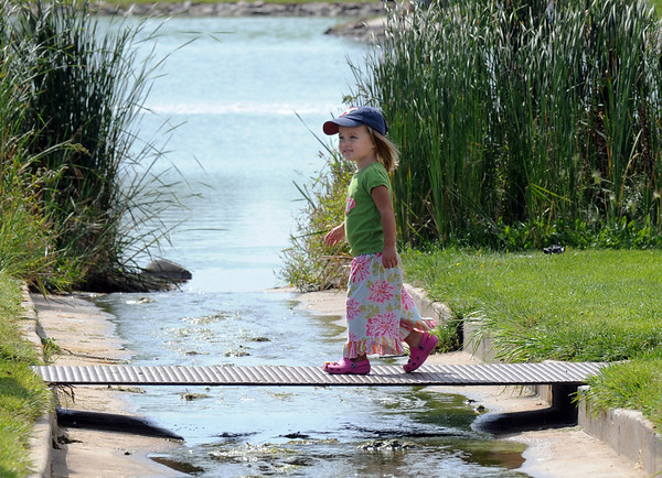 Elle Gray, 2, walks across a small bridge to go fishing with her family at the Broomfield Optimist Club's Huck Finn-Becky Thatcher Fishing Derby on Saturday at the Trails Pond. <br /> <br /> August 29, 2009<br /> staff photo/David R. Jennings