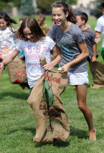Mikayla Goodman, 11, left, and Carlie Preskit, 11, try to keep their balance in the three legged race at the Broomfield Optimist Club's Huck Finn-Becky Thatcher Fishing Derby on Saturday at the Trails Pond. <br /> <br /> August 29, 2009<br /> staff photo/David R. Jennings