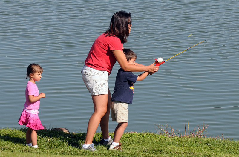 Mellisa Williams, center, helps her son Matthew, 4, with casting while daughter Miah, 2 1/2, left, watches during the Broomfield Optimist Club's Huck Finn-Becky Thatcher Fishing Derby on Saturday at the Trails Pond. <br /> <br /> August 29, 2009<br /> staff photo/David R. Jennings