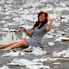 A racegoer sits amongst the rubbish after Aintree Ladies Day at the Grand National horse race meeting at Aintree racecourse in Liverpool, England, Friday April 9, 2010. (AP Photo/Tim Hales)