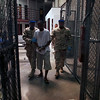 "In this March 30, 2010 photo, made through one way glass, reviewed by the U.S. military, a Guantanamo detainee carries a workbook as he is escorted by guards after the detainee attended a class in ""Life Skills,"" inside Camp 6 high-security detention facility at Guantanamo Bay U.S. Naval Base, Cuba. The Obama Administration is pushing to close the Guantanamo detention facility by transferring, prosecuting, or releasing the remaining detainees. (AP Photo/Brennan Linsley)"