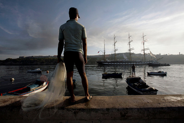 Fishermen watch as Russia's vessel Kruzenshtern, carrying a photo exhibition, arrives to the port of Havana, Friday, April 9, 2010. The Kruzenshtern was built in 1926 and in spite of its age, is one of the jewels of the Russian sailing fleet. (AP Photo/Franklin Reyes)