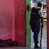 A man sleeps on the floor as a police officer patrols in Port-au-Prince, Friday, April  9, 2010.  Haitian authorities are trying to take control of the capital's slums from heavily armed gangs nearly three months after the earthquake destroyed police stations and allowed thousands of prisoners to go free. (AP Photo/Ramon Espinosa)