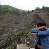 A woman reacts after a landslide destroyed her house in Niteroi on the outskirts of Rio de Janeiro, Friday, April 9, 2010.  Crews pulled at least 17 bodies from the debris at the site. More rain fell early Friday in Rio, threatening more landslides. (AP Photo/Felipe Dana)
