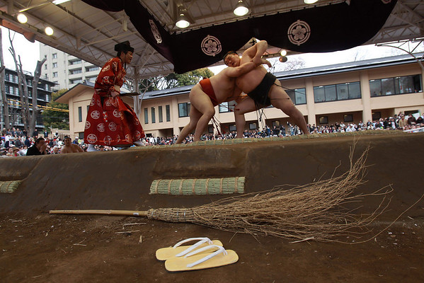 A broom and the slippers of a sumo referee lie against the ring during an exhibition match at Tokyo's Yasukuni Shrine during an annual spring festival ceremony Friday, April 9, 2010. The Yasukuni Shrine is a Shinto shrine which commemorates Japan's war dead. (AP Photo/David Guttenfelder)