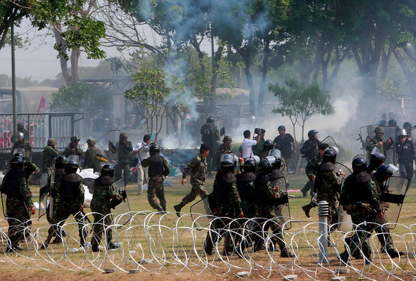 Thai soldiers run away from tear gas thrown back to them by protesters and supporters of ousted Prime Minister Thaksin Shinawatra after protesters storm the Thaicom satellite station Friday, April 9, 2010 in Pathum Thani province, Thailand. (AP Photo/Apichart Weerawong)