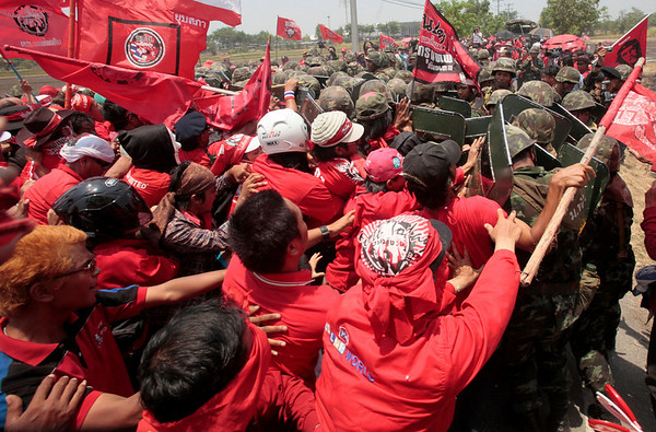 Anti-government protesters, left, push Thai soldiers back after Red Shirts stormed into the Thaicom teleport center in Pathum Thani province, north of Bangkok, Friday April 9, 2010. (AP Photo/Sakchai Lalit)