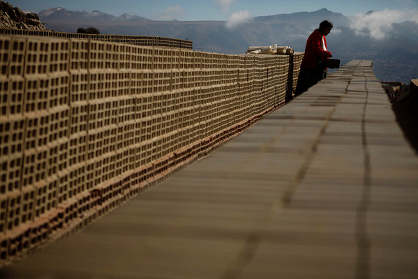 An Aymara indigenous woman dries bricks in the sun in the Achocalla neighborhood in La Paz, Thursday, April 8, 2010.  Achocalla is home to dozens of makeshift ovens that supply the city's growing construction industry with building materials. (AP Photo/Dado Galdieri)