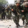 Thai soldiers protect themselves from stones thrown by anti-government protesters in Pathum Thani, north of Bangkok, Thailand, Friday, April 9, 2010. Anti-government protesters stormed into a telecom company compound where authorities had shut down their vital TV channel, as soldiers and riot police tried to hold them back with tear gas and water cannons. (AP Photo/Wason Waniichakorn)