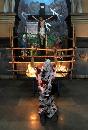 An Indian Catholic prays before an image of Jesus at a church in Calcutta, India, Thursday, April 1, 2010. (AP Photo/Bikas Das)