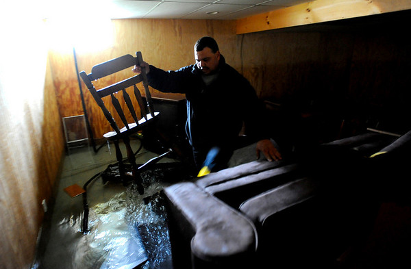 "Eddie Flynn, of Cranston, R.I., moves furniture from his wet basement as the flood water slowly recedes from his home in Cranston, R.I., Thursday, April 1, 2010. Rhode Island Gov. Don Carcieri calls the worst flooding to hit the state in 200 years ""another whack"" at Rhode Island's dismal economy. (AP Photo/Gretchen Ertl)"