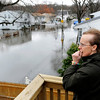 Beverly Van Slyke, of Cranston, R.I., surveys a flooded street from a neighbor's deck in Cranston, R.I., Thursday, April 1, 2010. Rhode Island is struggling to cope with the worst flooding in 200 years. (AP Photo/Gretchen Ertl)