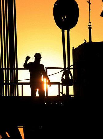 A worker signals on a new oil rig at sunset Thursday, April 1, 2010, in the Persian Gulf desert oil field of Sakhir, Bahrain. Oil prices rose above $84 a barrel Thursday, extending a two-month rally amid surging regional stock markets ahead of the Good Friday holiday. (AP Photo/Hasan Jamali)