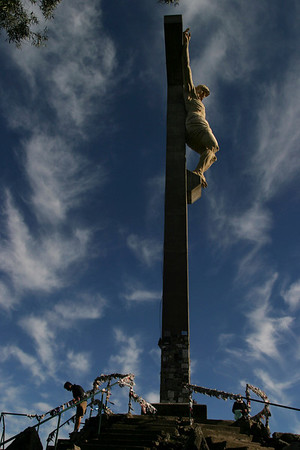 People walk past a cross with an statue of Jesus Christ during a Holy Week procession in Tandil, Argentina, Thursday, April 1, 2010. (AP Photo/Pablo Aneli)