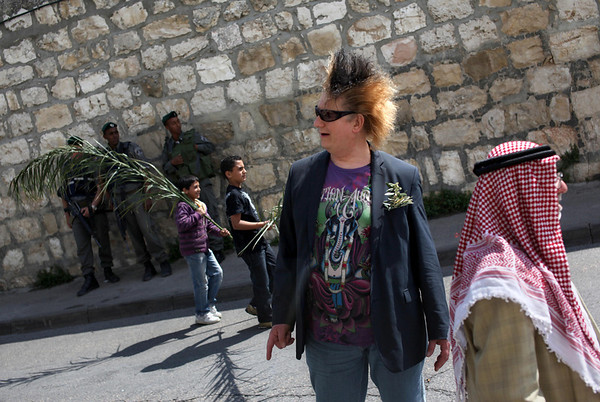Palestinians and a tour guide, center, are seen next to Israeli policemen during the traditional Palm Sunday procession in Jerusalem Sunday, March 28, 2010. Palm Sunday commemorates Jesus Christ's triumphant entry into Jerusalem, and is the start of the Christian Holy Week. (AP Photo/Oded Balilty)