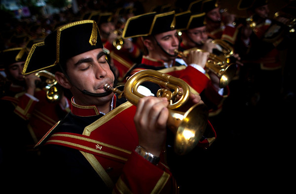 "Musicians from the ""El Despojado"" brotherhood blow their horns as they take part in a procession in Seville, southern Spain, Sunday, March 28, 2010. Hundreds of processions take place throughout Spain during the Easter Holy Week. (AP Photo/Emilio Morenatti)"