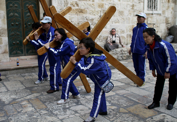 A Christian pilgrim from South Korea, right, waits her turn to pose with a wooden cross with others outside the Church of the Holy Sepulchre in Jerusalem's Old City, Thursday, March 25, 2010. Christian Holy Week begins Sunday March 28, 2010. (AP Photo/Tara Todras-Whitehill)