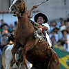 An Uruguayan gaucho, or cowboy, rides a horse during a rodeo in Montevideo, Sunday, March 28, 2010. Every year, during Holy Week, hundreds of gauchos show their skills and compete for the title of best rider of the rodeo. (AP Photo/Matilde Campodonico)